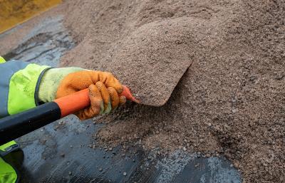 Grit team worker shoveling grit