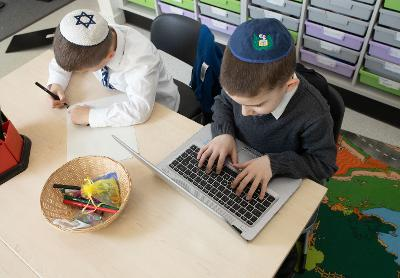 Pupils writing and using laptop
